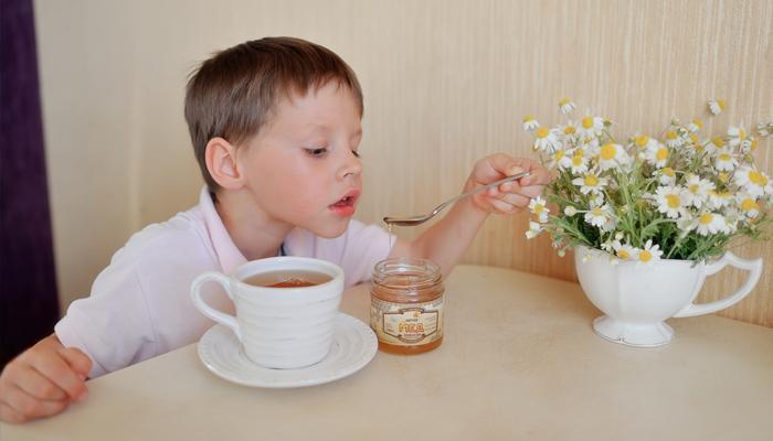 Ребенок пьет чай с медом